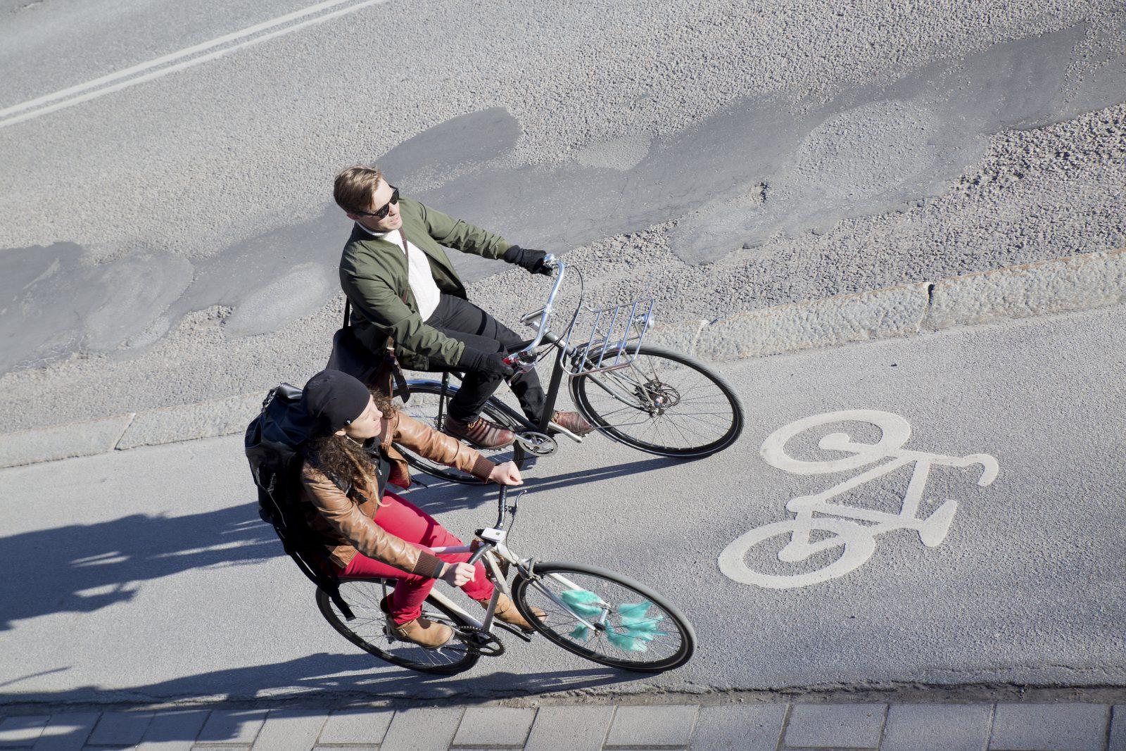 Två personer cyklar på cykelväg i Stockholm.