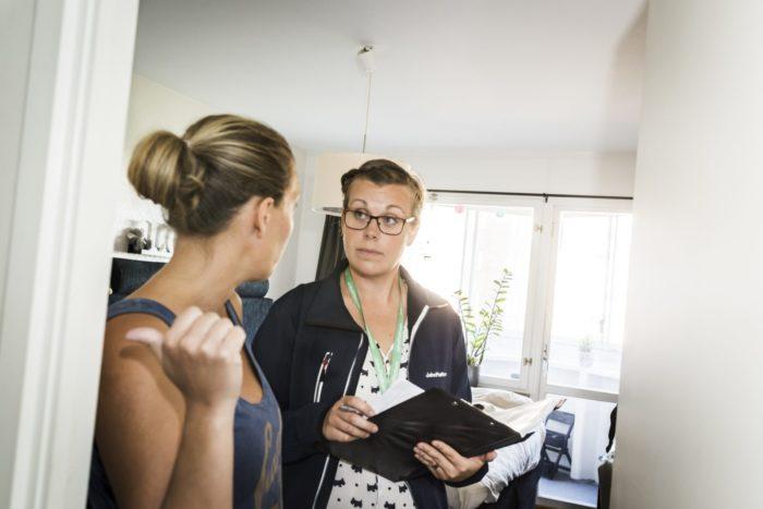 John Mattsons medarbetare i arbetskläder lyssnar på en hyresgäst som pekar och förklarar i sin lägenhet.