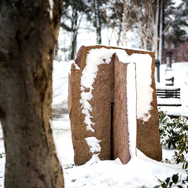 Kantig stenskulptur delvis täckt av snö.