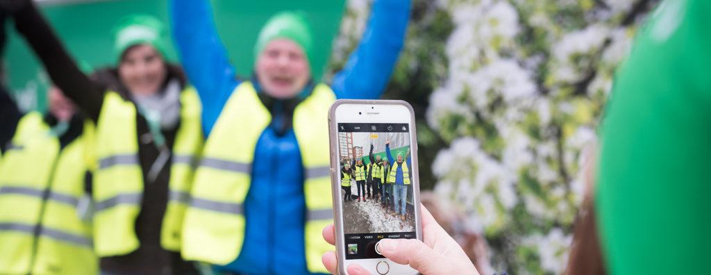 En grupp av John Mattsons medarbetare klädda i varselvästar poserar med uppsträckta armar för en fotografering framför en byggarbetsplats.