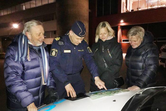 Fyra personer står utomhus och tittar på en karta som ligger på motorhuven till en polisbil.