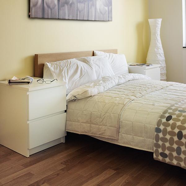 En bäddad säng i ett sovrum utan mattor på golvet.