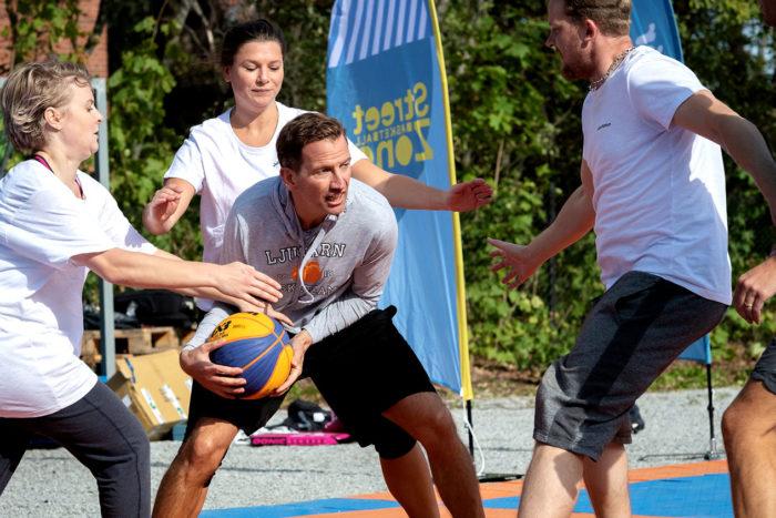 Flera av John Mattsons medarbetare blockerar Jacob från Lidingö Basket under en match i streetbasket i Larsbergsparken.