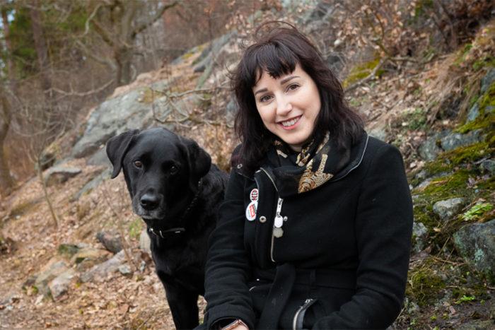 Mörkhårig kvinna med stor svart hund på skogsstig. Båda tittar in i kameran.