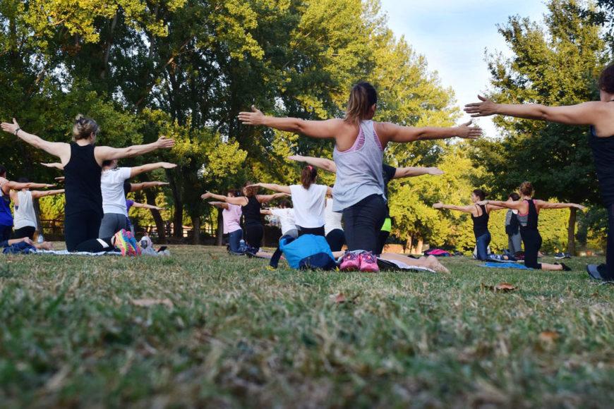 Kvinnor tränar yoga i park.
