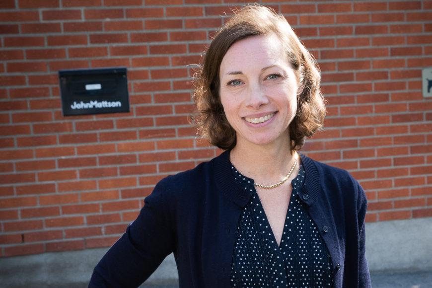 Kvinna i prickig klänning och mörkblå tröja framför tegelvägg med John Mattsons logotyp på. Kvinnan ler mot kameran.
