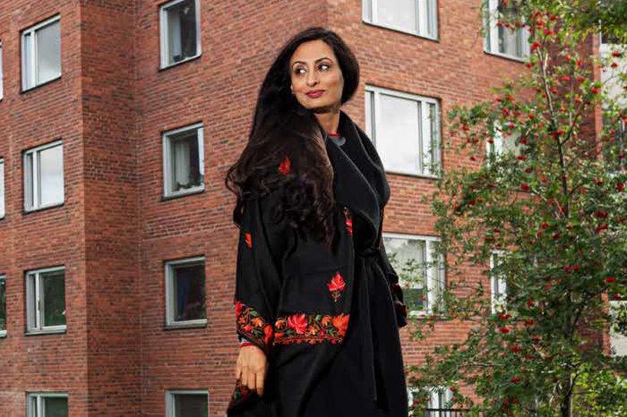 Kvinna i kappa promenerar framför tegelhus och buskage.