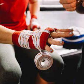 Kampsportsutövare får sin hand lindad med boxningstejp.