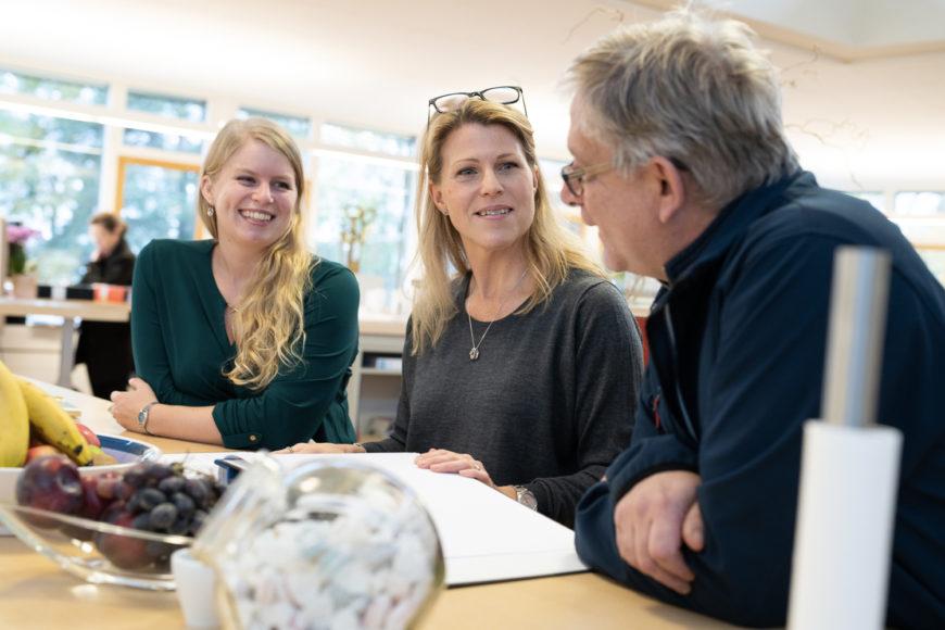 Tre kollegor i samtal vid ett fikabord
