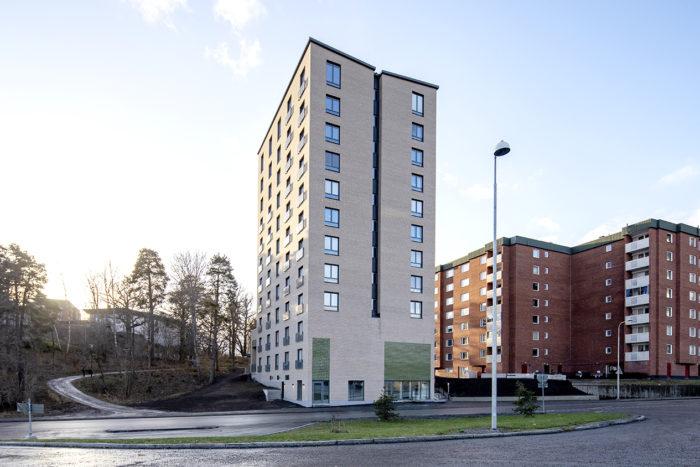 Nybyggd höghus med ljus tegelfasad framför äldre och mörkare tegelhus.