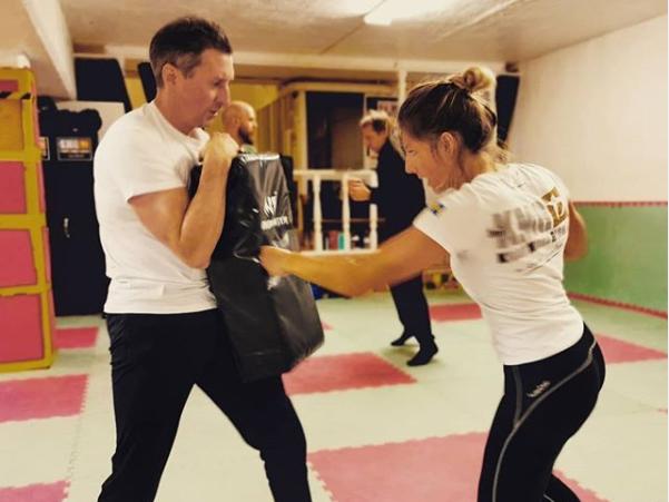 En man och en kvinna tränar kampsport.