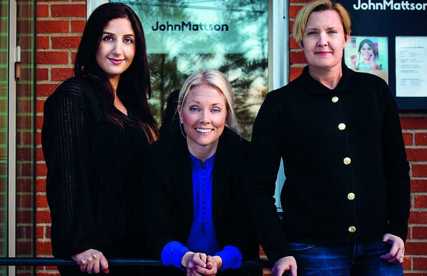 Tre kvinnor poserar framför en tegelvägg till en kontorsbyggnad.