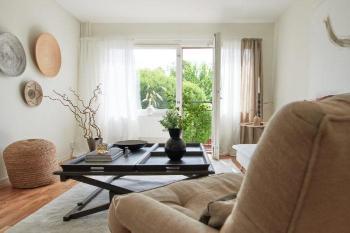 Ljust och välstädat vardagsrum med skira gardiner och balkongdörren på glänt.