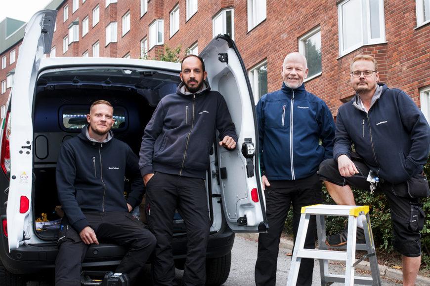 Fyra män i mörkblå arbetskläder poserar framför en hantverksbil utomhus.